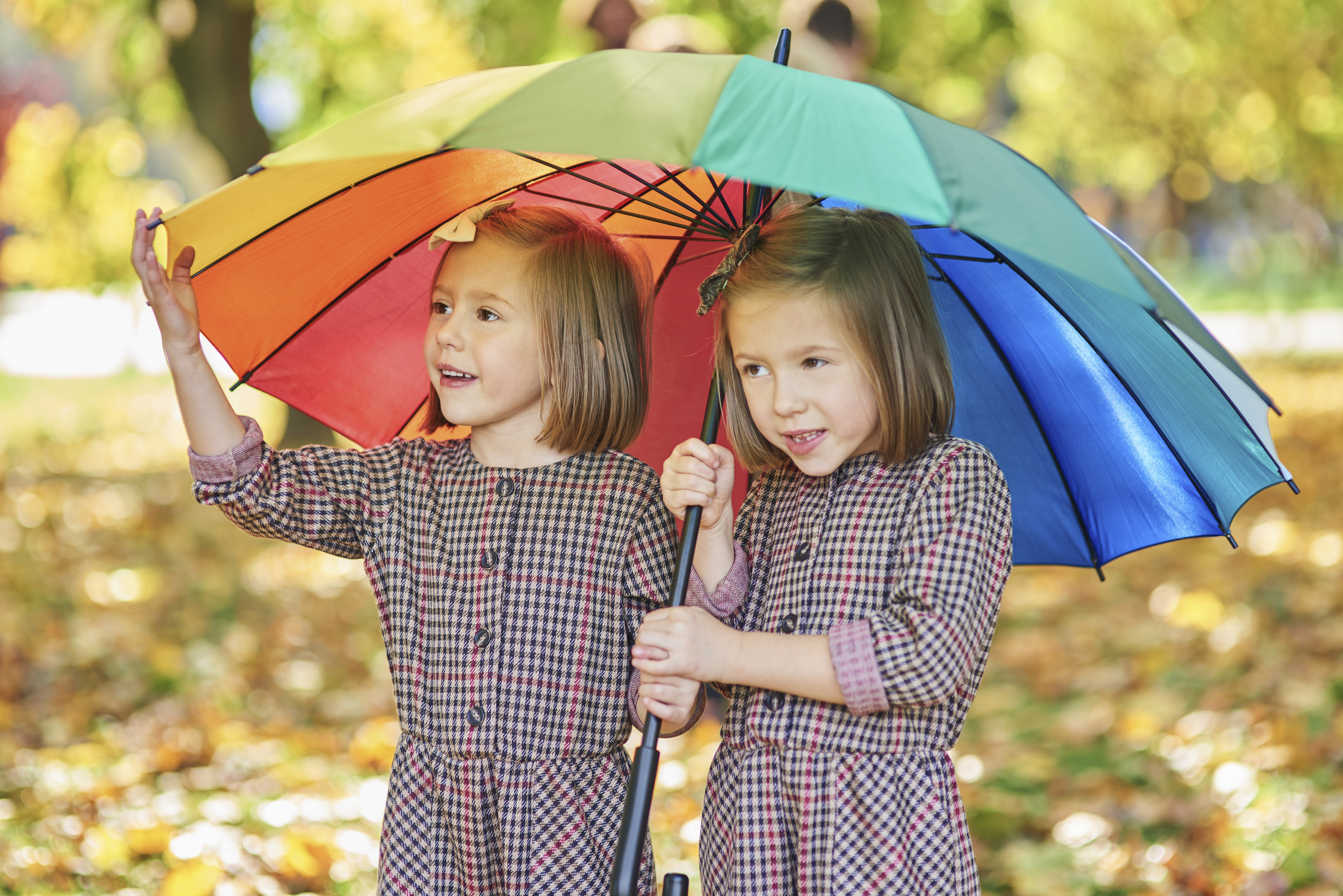 twins-looking-for-shelter-with-umbrella-5L53NKK